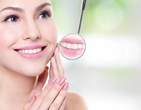 Atraktivní usmívající se žena tvář s zdraví zubů zblízka a zubař ústech zrcadlo, koncept péče o chrup