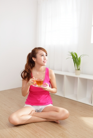 chinese meal: Beautiful Young Woman drinking hot tea at home with wood floor in the morning, healthy lifestyle concept, asian beauty