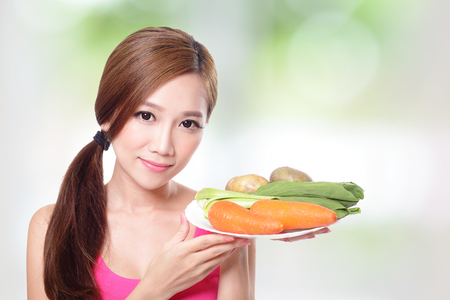Happy young woman holding green vegetables and carrots isolated on green photo