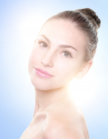 Close up portrait of beautiful young woman face. Isolated on blue background. Skin care or spa concept photo