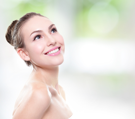 attractive smiling woman face with health teeth close up , copy space on the right side. Isolated over green background Stock Photo
