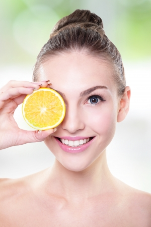 Beautiful woman face with juicy orange, green background photo