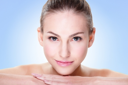 Close up portrait of beautiful young woman face while lying. Isolated on blue background. Skin care or spa concept