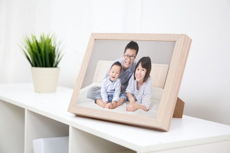 Happy Family photo on white bookshelf at home Stock Photo - 25306380