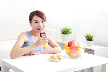 c vitamin: Cheerful woman drinking an orange juice sitting on her sofa at home, asian beauty