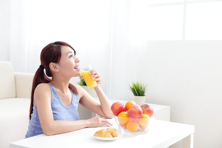 Mujer alegre que bebe un jugo de naranja sentado en el sofá en casa Foto de archivo