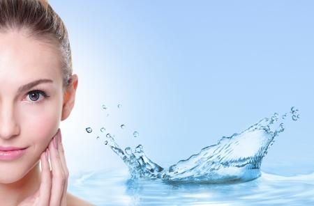 Mooie vrouw gezicht met water spatten geïsoleerd op blauwe achtergrond Stockfoto