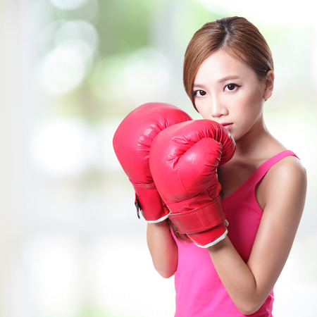 punched: Fit woman boxing isolated over green, asian