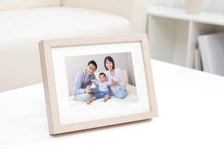 frame photo: Happy Family photo on white bookshelf at home Stock Photo
