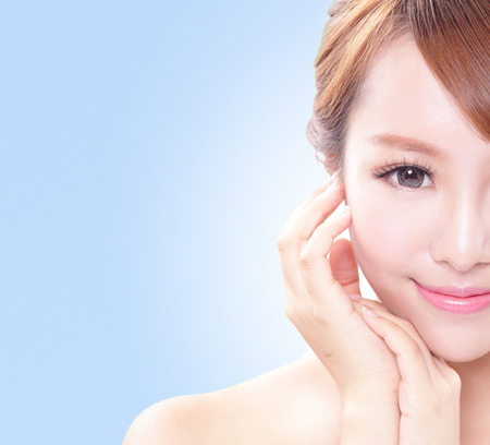 chin on hands: portrait of the woman with beauty face and perfect skin isolated on blue, asian beauty Stock Photo
