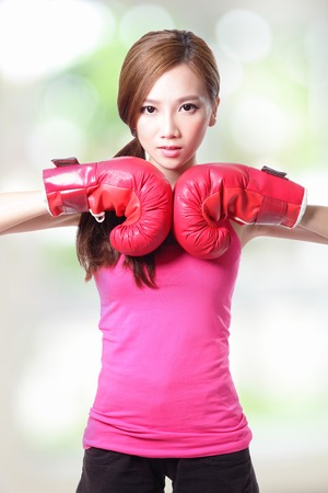 Fit woman boxing isolated over green, asian photo