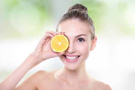 Beautiful woman face with juicy orange, green  photo