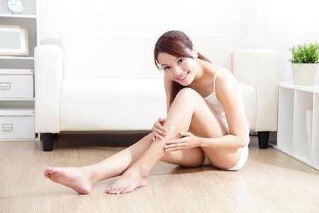 Krása mladá hezká žena s perfektním stavu a používání krému na její atraktivní nohy doma doma, asijské krásy