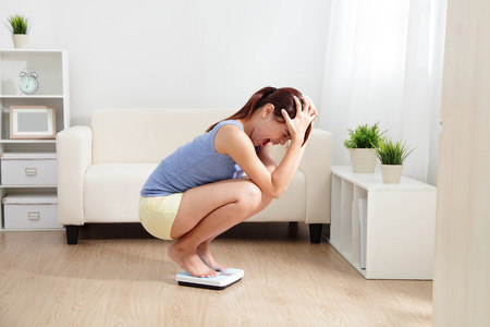 sad faces: Upset woman on weigh scale at home, asian