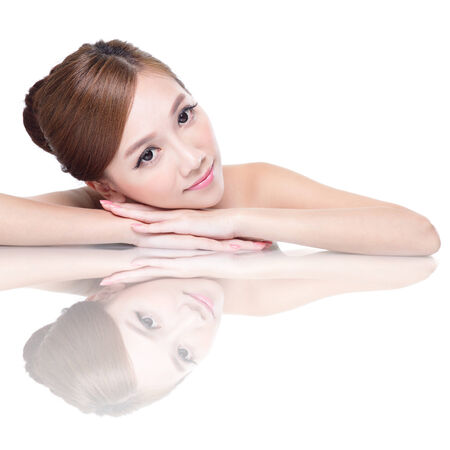Beautiful face skincare beauty woman lying down with mirror reflection isolated on white background. asian photo