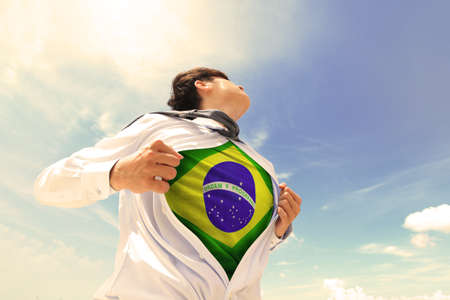 Business man pulling his t-shirt open, showing Brazil national flag, retro color tune photo
