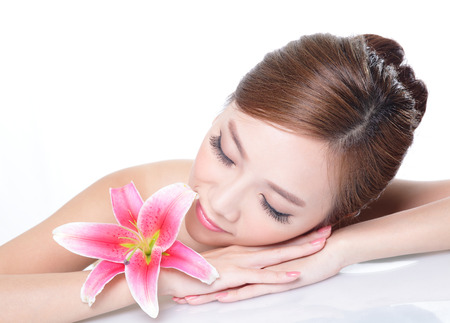 Beautiful face skincare beauty woman lying down with pink lily flower and mirror reflection. asian photo