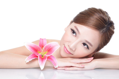 Beautiful face skincare beauty woman lying down with pink lily flower and mirror reflection. asian Stock Photo