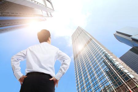 gelukkig succesvol zakenman buiten naast kantoorgebouwen met stadsbeeld en hemel, hong kong, Azië, Aziatisch