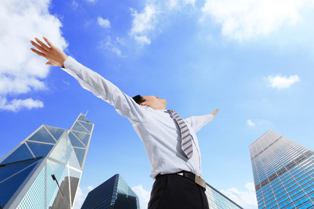 Business man carefree outstretched arms with sky and city background, asian photo