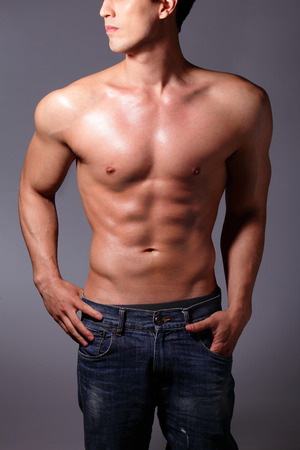 abdomens: Sexy muscular young man. Isolated on gray background. asian and european mixed blood