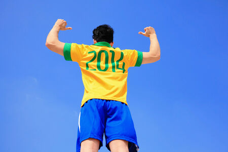 Brazilian football player with 2014 shirt  with blue sky photo