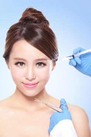 Close up of cosmetic injection to the pretty woman face. Isolated on blue , asian photo
