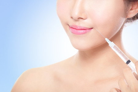 Relaxed beautiful woman having an injection above the lips isolated on white , asain photo