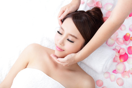 Bella giovane donna godere di massaggio fronte alla stazione termale con le rose, asiatico bellezza