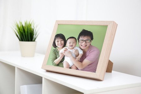 Happy Family photo on white bookshelf at home Stock Photo