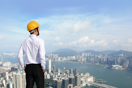 Young architect wearing a protective helmet looking the city building outdoor  photo