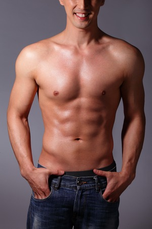 asian abs: Sexy muscular young man. Isolated on gray . asian and european mixed blood Stock Photo