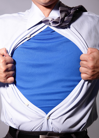 superman: Business man pulling his t-shirt open, showing a  suit underneath his suit Stock Photo