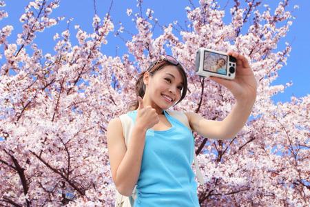 flor de sakura: Mujer feliz foto de un viajero por la cámara con el árbol de sakura de vacaciones en Japón Foto de archivo