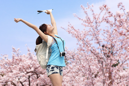 Happy woman traveler photo by camera with sakura tree on vacation in japan photo