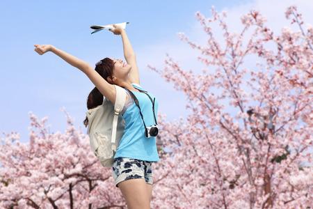 osaka: Happy woman traveler photo by camera with sakura tree on vacation in japan Stock Photo