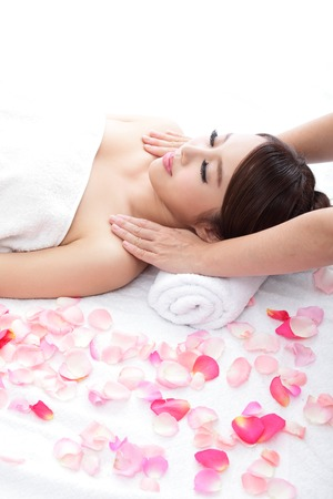 Beautiful woman smile getting massage and spa treatment on shoulder with rose, asian beauty photo