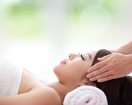 relax massage: Relax beautiful woman face receiving massage with nature green background, asian beauty