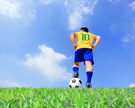 Brazilian soccer player man striking the ball at the stadium with blue sky photo
