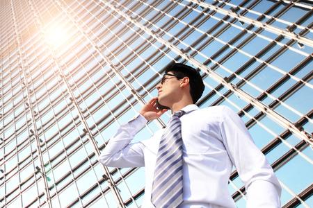 business smile: Hombre de negocios hablando por tel�fono inteligente en la ciudad