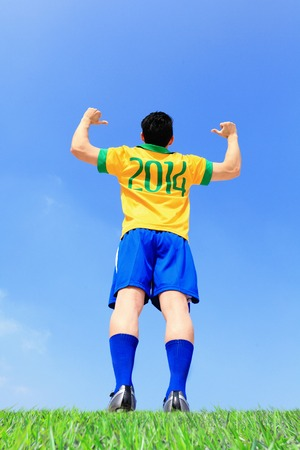 Brazilian soccer football player with 2014 shirt look blue sky on field photo