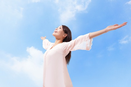 aire puro: Mujer hermosa que se respira aire fresco, con los brazos en alto con un cielo azul y nubes en el fondo Foto de archivo