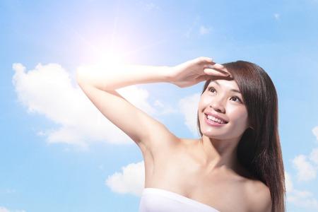 Cara de mujer hermosa con el sol y el cielo azul, el concepto de cuidado de la piel y protector solar, belleza asiática
