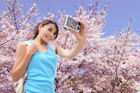 Happy woman traveler photo by camera with cherry blossoms tree on vacation photo