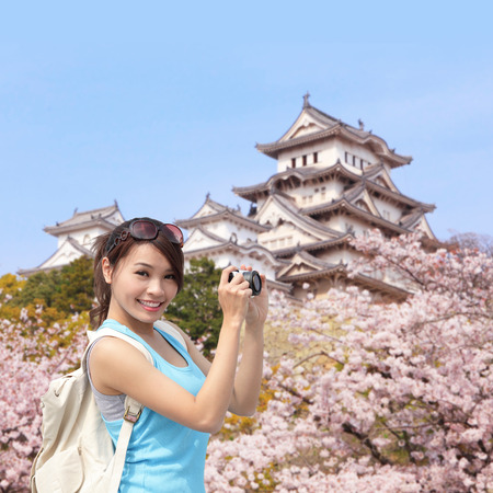 osaka castle: Happy woman traveler take photos by camera with cherry blossoms tree and castle on vacation while spring