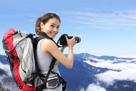 Young woman with backpack taking a photo on the top of mountains, asian photo