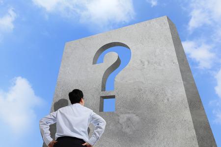 signo de pregunta: Hombre de negocios que mira la pared del signo de interrogaci�n