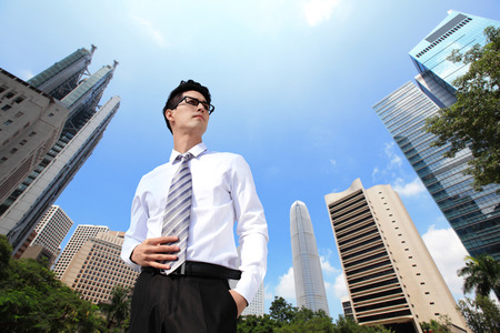 Successful handsome business man purposefully looking away with blue sky in the city photo