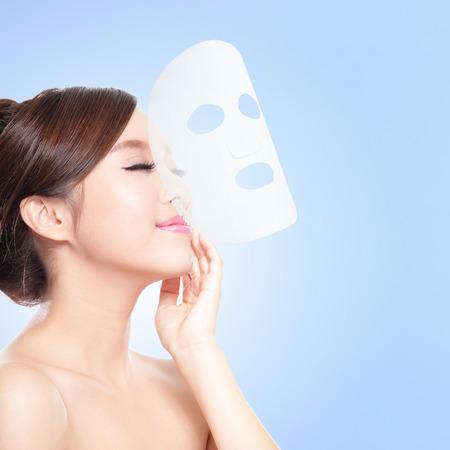 Entspannen Junge Frau mit Tuch-Gesichtsmaske isoliert auf blauem Hintergrund, das Konzept für die Hautpflege und Sonnenbrand-Schutz, asiatische Schönheit Standard-Bild - 27090225