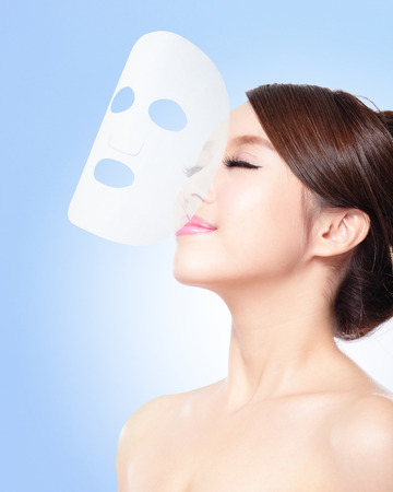 Relax Young woman with cloth facial mask isolated on blue background, concept for skin care and sunburn protection, asian beauty